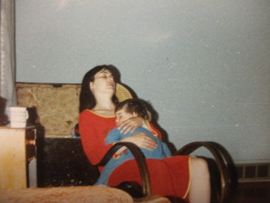 Lynette Louise closing her eyes with her youngest son in her arms.